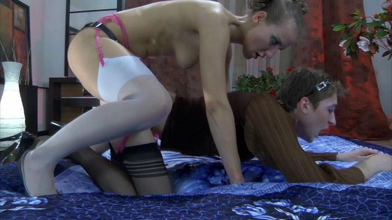 Barbara fourre la bite de son gode ceinture entre les levres peintes de  son male féminisé